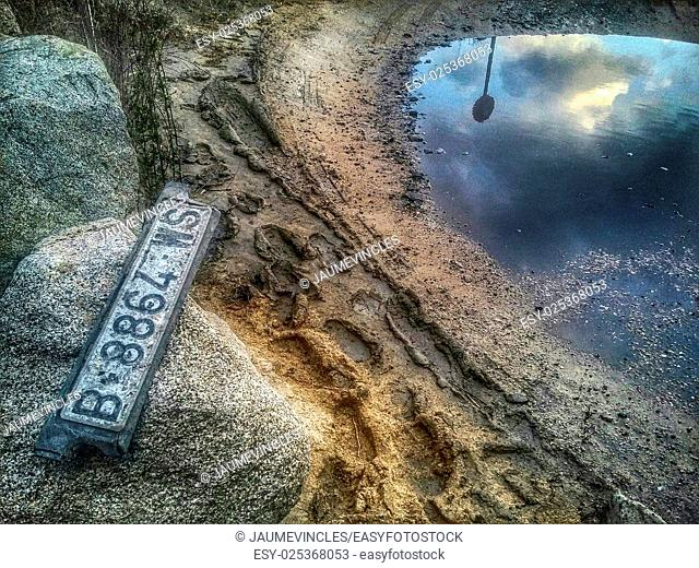 Abandoned car license plate and reflection in puddle. Arenys de Mar, Maresme, Barcelona province, Catalonia, Spain