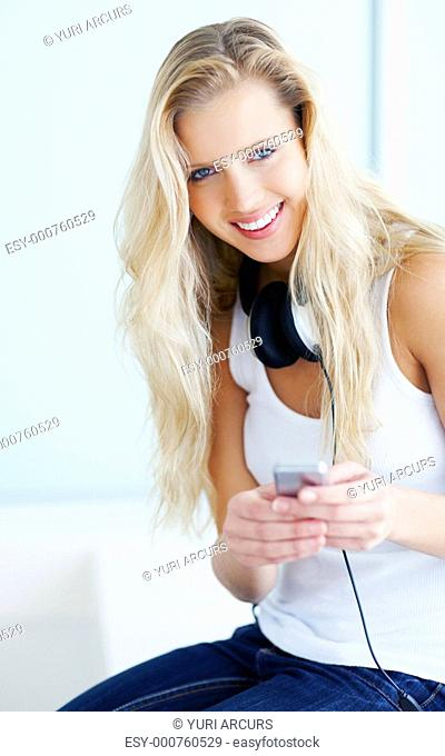 Attractive young woman with MP3 player and headphones smiling