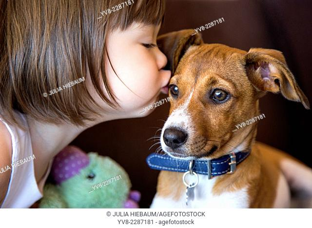 Toddler girl kissing her puppy dog