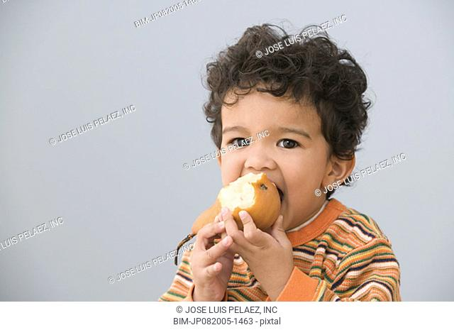 Portrait of young boy eating pear