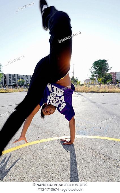 Breakdancer John Lartey performs a handstand in the street