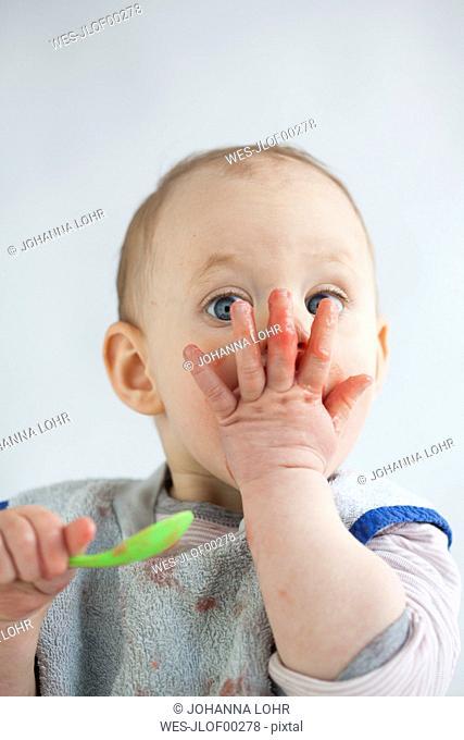Portrait of baby girl eating mush