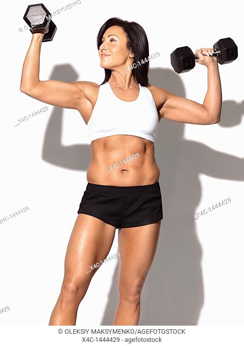 Portrait of a smiling fitness woman with dumbbells in her forties  Isolated on white background