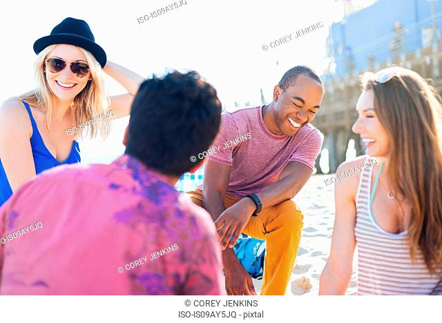 Four adult friends chatting on beach, Santa Monica, California, USA