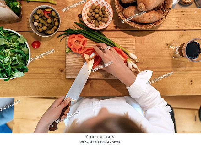 Woman chopping bell pepper in the kitchen, top view