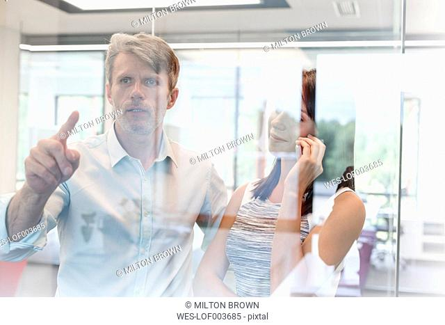 Business people in office touching glass screen