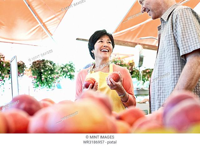 Smiling woman wearing apron and man standing at stall with fresh peaches at a fruit and vegetable market