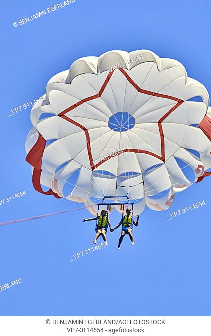 Couple during parasailing adventure, flying in sky. Chersonissos. Crete, Greece