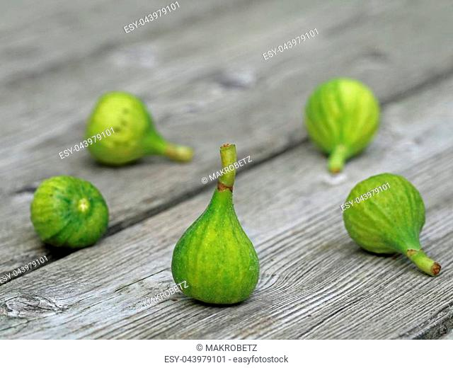 five little green figs on wooden background