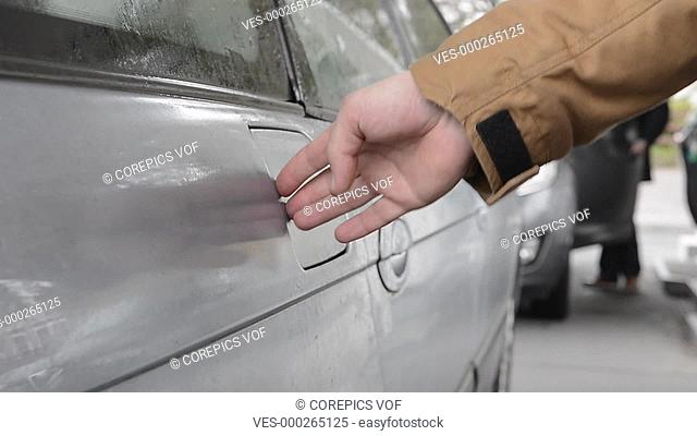 Hand, opening the fuel cap of a vehicle at a petrol station