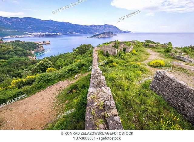 Ruins of 19th century Austrian Mogren Fortress in Budva city on the Adriatic Sea coast in Montenegro. Aerial view with Sveti Nikola Island