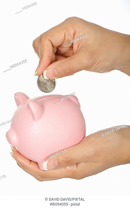Woman holding a piggy bank and placing a quarter into it