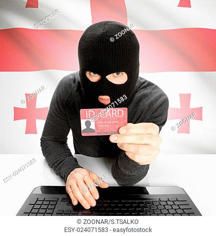Hacker with flag on background holding ID card in hand - Georgia