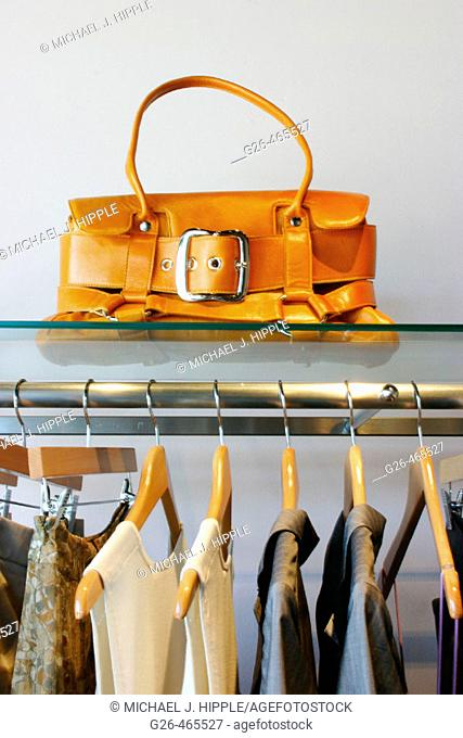 Purse and rack of clothes at hip boutique