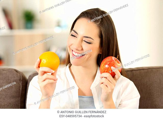 Happy woman deciding between different fruits sitting on a couch in the living room at home