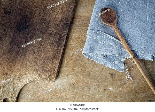cutting board and a wooden spoon on the table, top view, an empty space in the middle