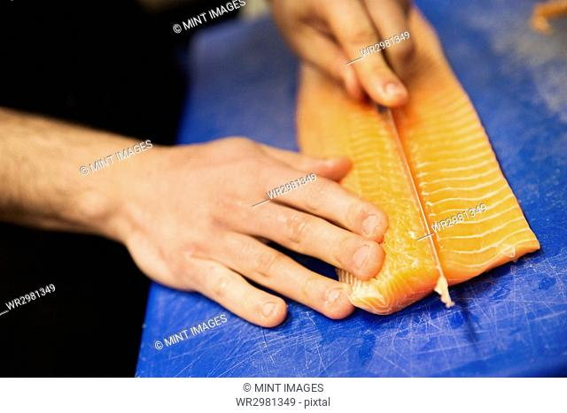 Close up high angle view of person, cutting a fillet of salmon on a blue chopping board