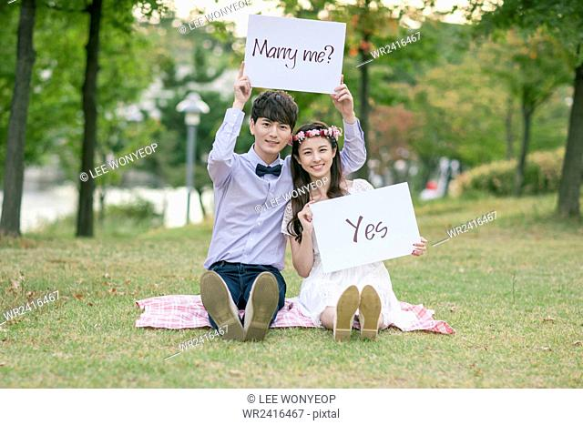Bride and groom holding a message of marry me and yes both seated on a grass