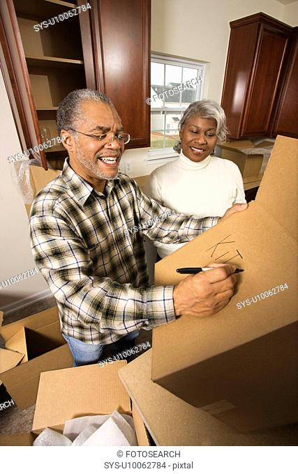 Middle-aged African-American male labeling moving box with wife in background