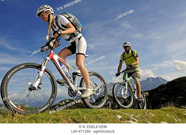 Mountain bikers passing Steiplatte, Lofer Mountains in background, Tyrol, Austria