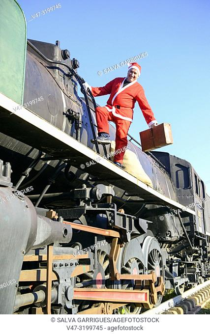 Santa Claus with a suitcase goes on travel trip in a steam train locomotive