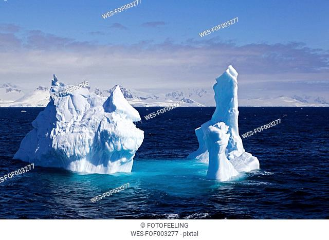 South Atlantic Ocean, Antarctica, Antarctic Peninsula, Gerlache Strait, View of iceberg with snow-covered mountain range in background