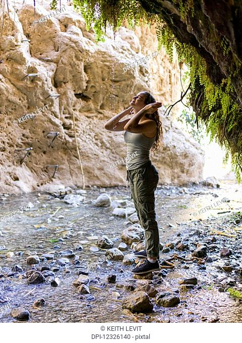 A young woman stands on a rock and looks up along a stream at Dodim Cave, Ein Gedi Nature Reserve; South District, Israel