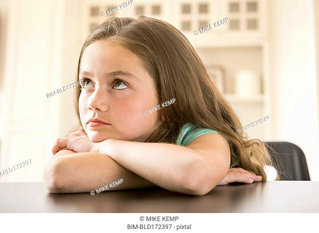 Bored Caucasian girl leaning on table