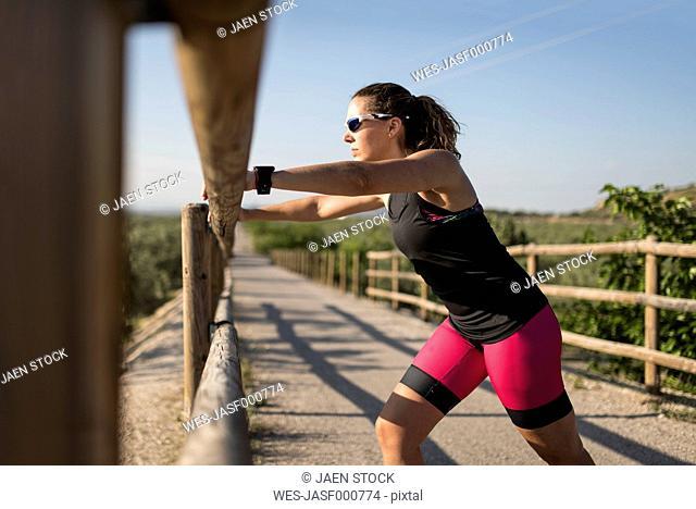 Sportive woman stretching on a bridge