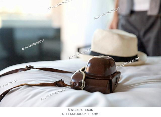 Camera and hat on bed