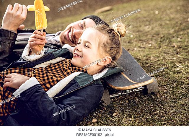 Father and daughter resting on skateboard, eating ice cream