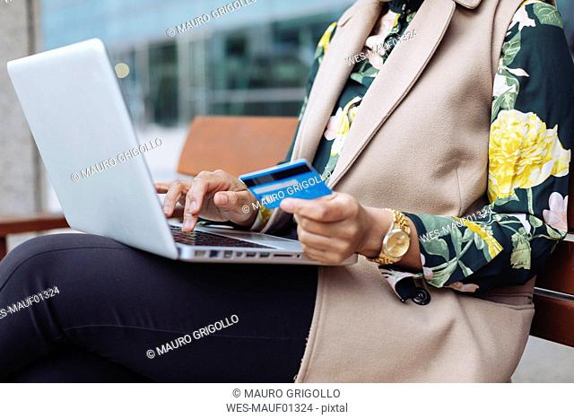 Businesswoman sitting on bench using laptop and credit card, partial view