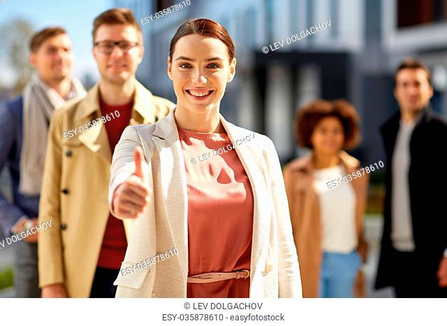 business, success and gesture concept - happy smiling woman with international group of people showing thumbs up outdoor