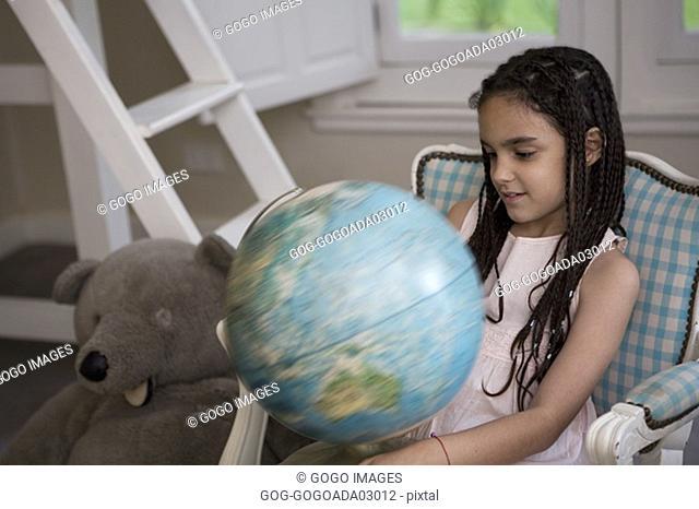 Young girl examining globe