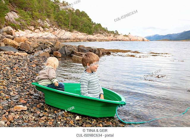 Boys in green boat at fjord water's edge, Aure, More og Romsdal, Norway