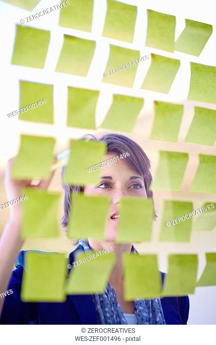 Female creative professional behind glass pane with adhesive notes