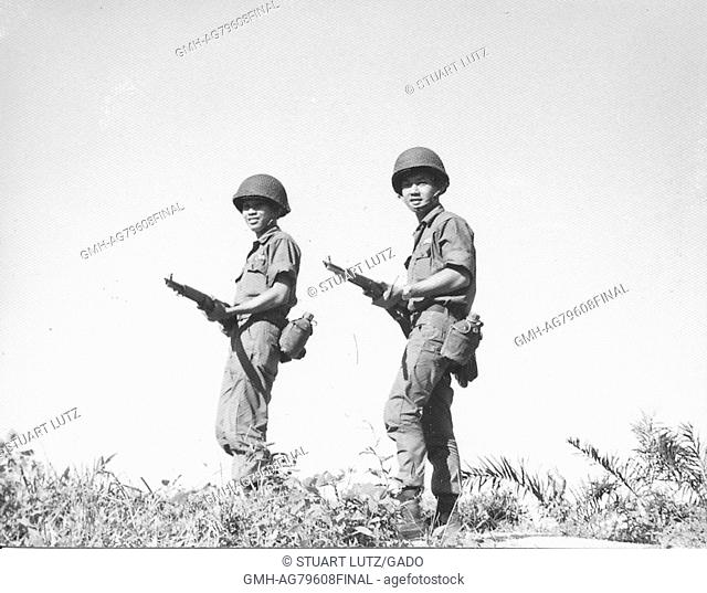 A photograph of two soldiers of the Army of the Republic of Vietnam, the are posed standing on a hill while holding their combat rifles at waist height, Vietnam