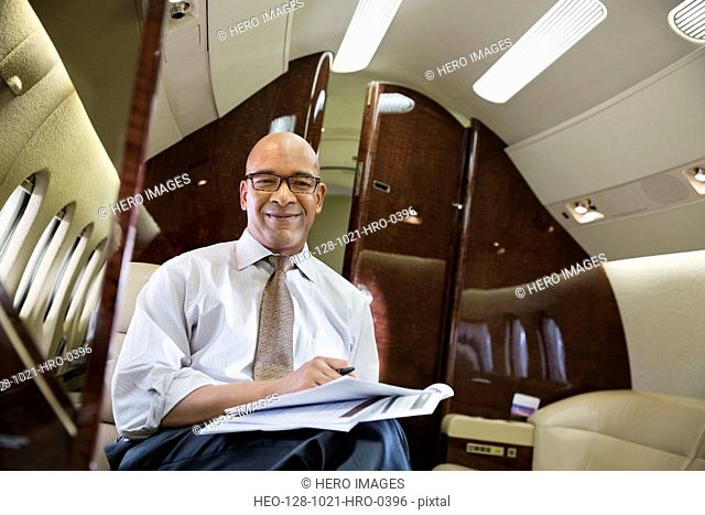 Portrait of businessman working on documents in airplane