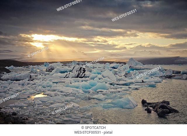 Iceland, South of Iceland, Joekulsarlon glacier lake, icebergs and sunshine through clouds