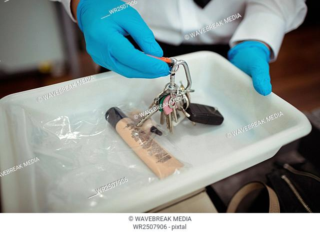 Security officer holding tray of liquid and key