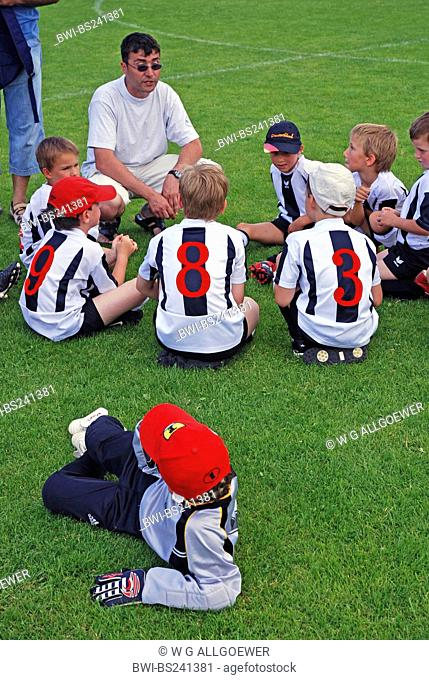 juvenile football coach at a tournament gathering his team on the lawn, Germany, Baden-Wuerttemberg