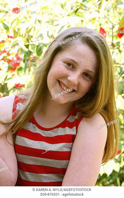 barely-teenage girl, long gold-brown hair, freckles, smiling at camera, wearing striped tank top, sunlit foliage behind