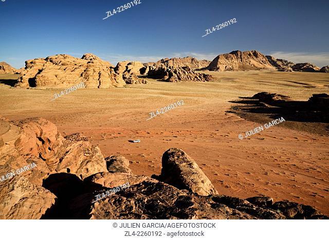 Car, red sand desert and rocks. Jordan, Wadi Rum desert, protected area inscribed on UNESCO World Heritage list