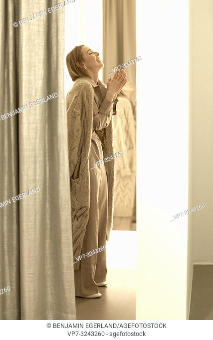 happy fashionable woman with folded hands inside fitting room of clothing store, wearing new stylish one-piece jumpsuit combined with beige coat