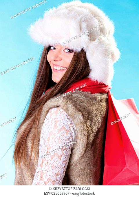winter woman in warm clothes fur cap with red paper shopping bag on blue. girl buying. sale and retail