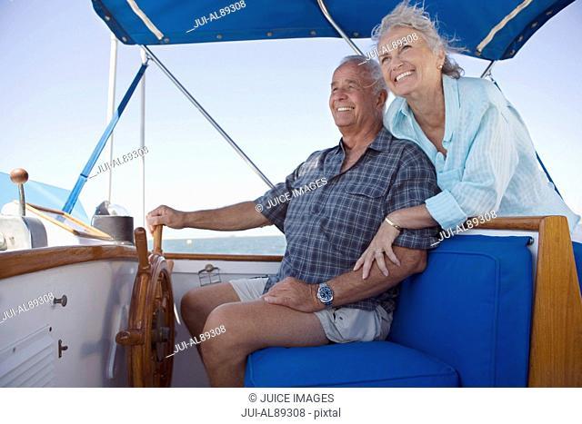 Senior couple sitting at helm of boat