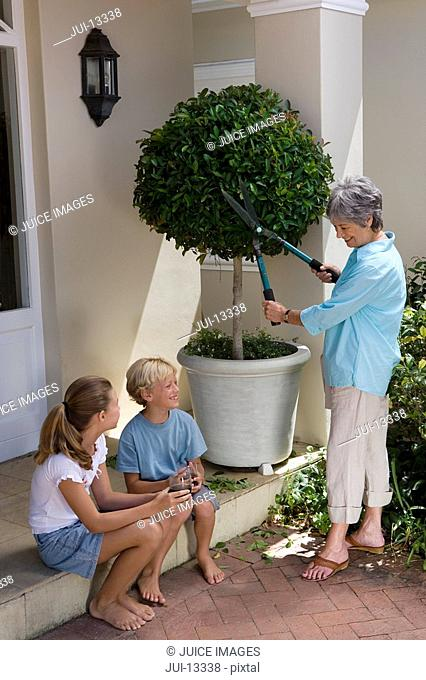 Mother pruning tree in pot, smiling at son and daughter 8-12