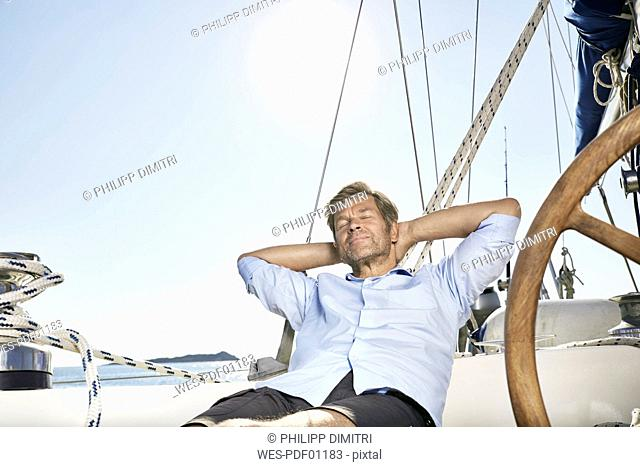 Portrait of smiling mature man relaxing on his sailing boat