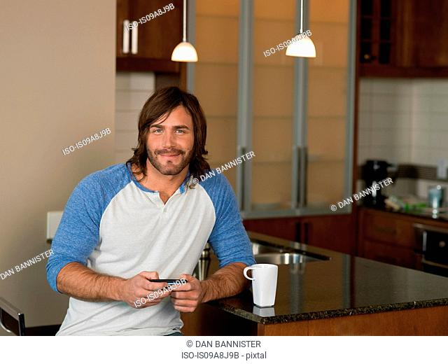 Mid adult man using mobile phone in kitchen, portrait