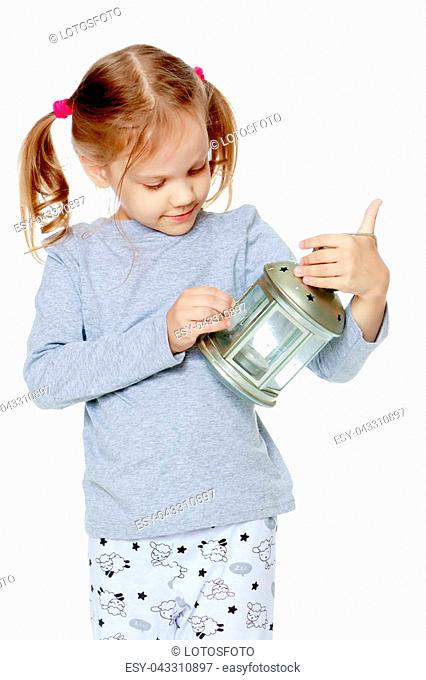 A little girl is holding a lamp. The concept of happiness, holiday, child, birthday, Christmas. Isolated on white background